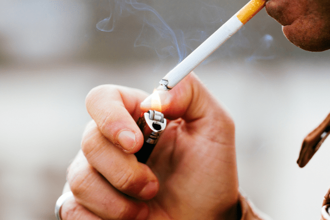 Man tänder en cigarett