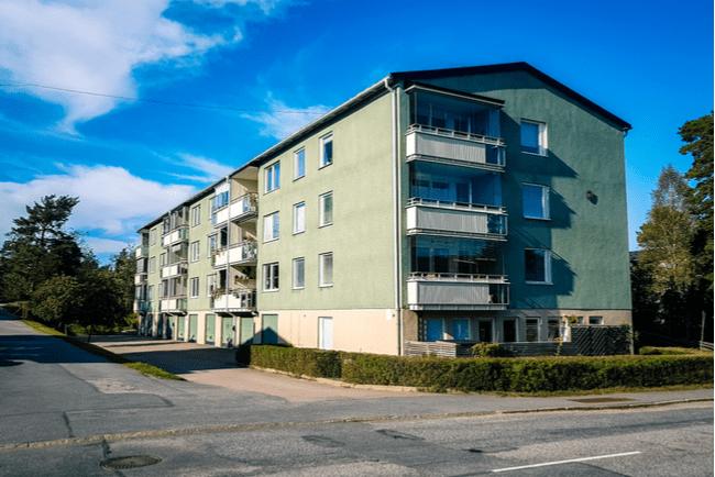 en bild på ett grönt lägenhetshus