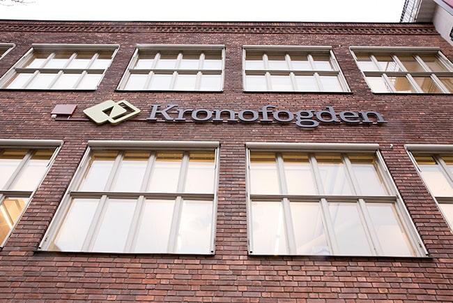 En bild på Kronofogdens logga på en fasad