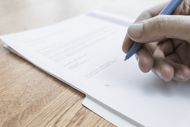 En bild på en man som skriver på ett kontrakt