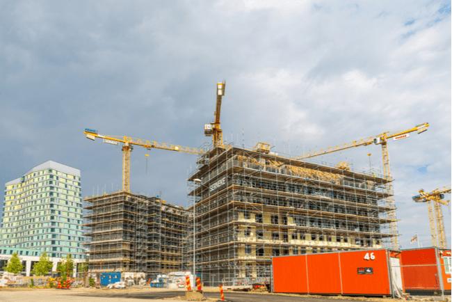 En bild på en byggarbetsplats med två lägenhetshus