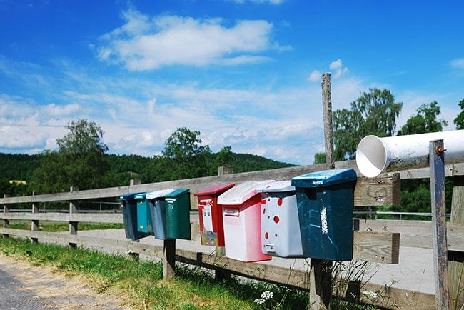 Brevlådor på ett stängsel intill en landsväg