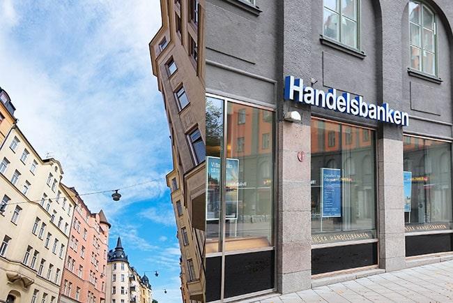 En bild på Handelsbankens logga och lägenhetshus