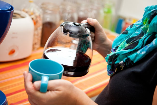 Kvinna häller upp kaffe i kaffekopp