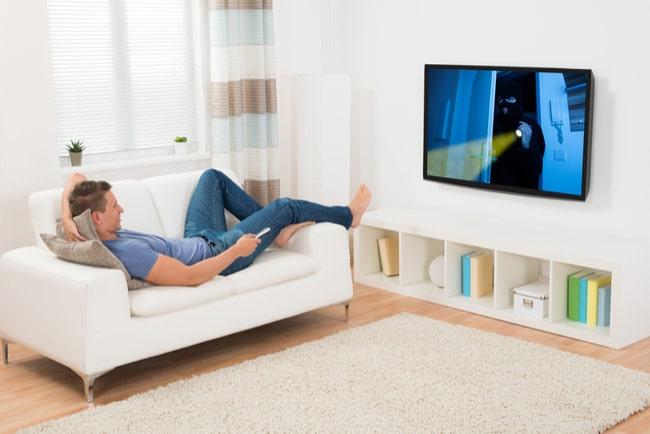 Man ligger i soffa och tittar på tv
