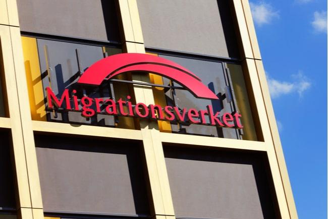 Migrationsverkets röda logga på en fasad