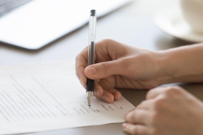 Person skriver på hyreskontrakt