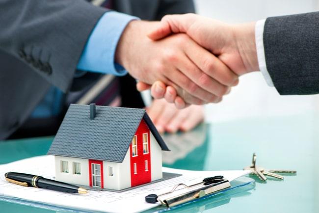 Mäklare skakar hand med kund över ett påskrivet kontrakt.