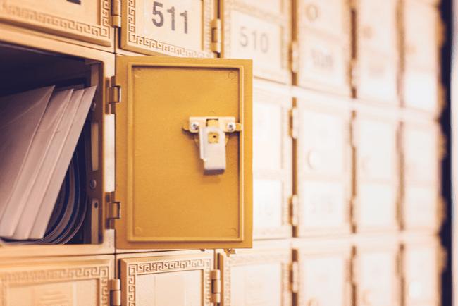 Gul postbox med brev i