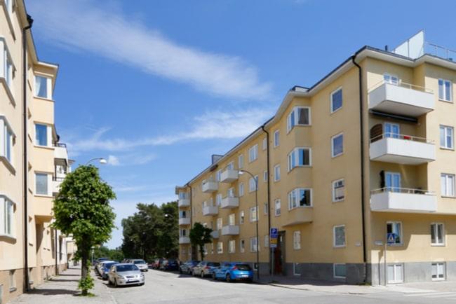 Gult flerfamiljshus med vita balkonger