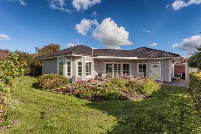 En grå villa med en stor gräsmätta