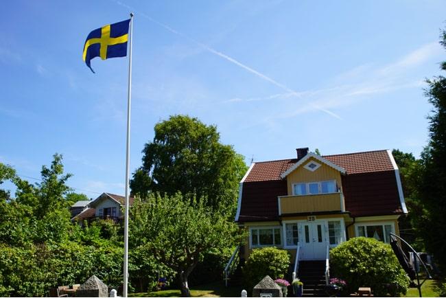 Gul villa med flaggstång med svensk flagga på tomten