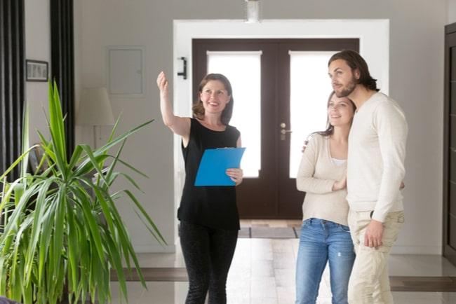 Kvinnlig mäklare visar par runt i lägenhet