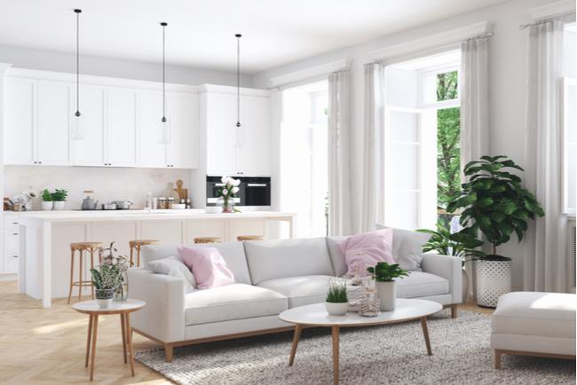 Ett möblerat vardagsrum med ett kök i bakgrunden