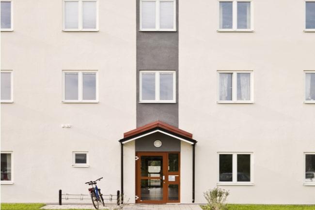 Vitt flerfamiljshus med brun dörr