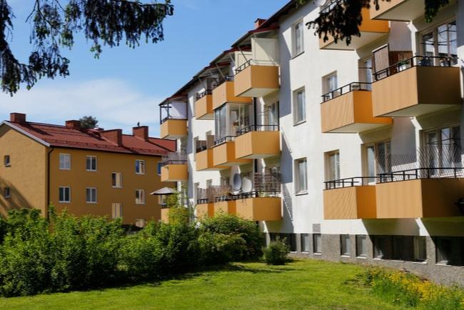 Vitt flerfamiljshus med orangea balkonger