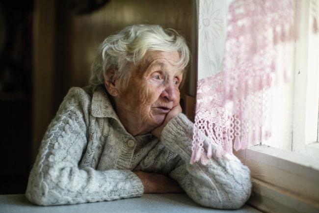 äldre kvinna sitter vid ett bord och tittar ut genom fönstret