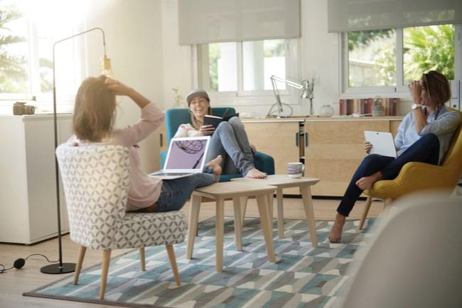 tre personer sitter och pratar i ett gemensamt allrum i lägenhet
