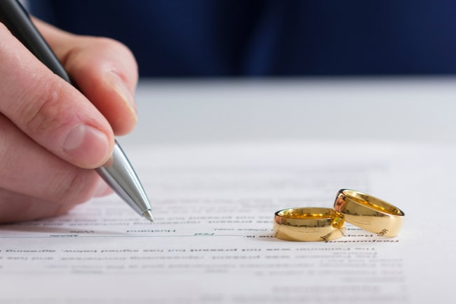 hand skriver på kontrakt med två vigselringar bredvid