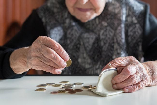 äldre kvinna räknar mynt ur en portmonnä