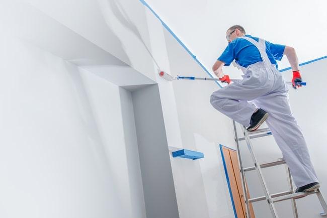 man målar en vägg inomhus ståendes på en stege