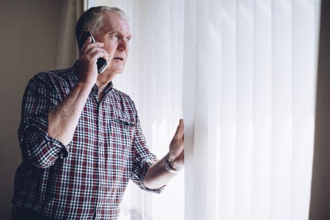 äldre man tittar oroligt ut genom fönstret medan han pratar i telefon