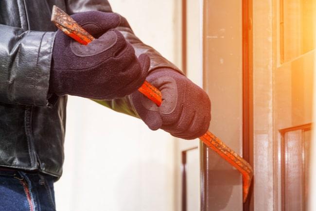 en inbrottstjuv dyrkar upp en dörr med kofot
