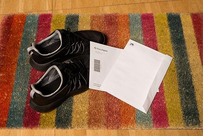 ett par skor och brev från kronofogden på en hallmatta
