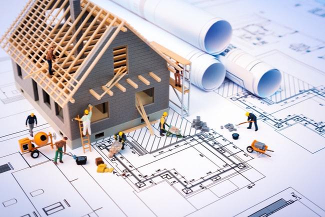 modell av husbygge med byggarbetare, på ritningar