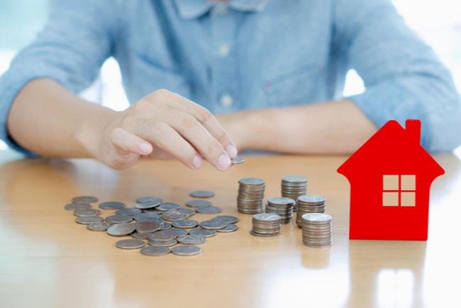 person staplar mynt i högar bredvid en siluett av ett hus