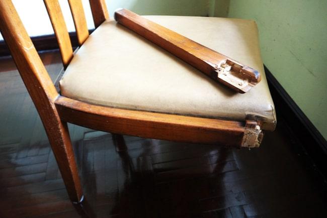 avbrutet stolsben ligger på sitsen på trasig stol