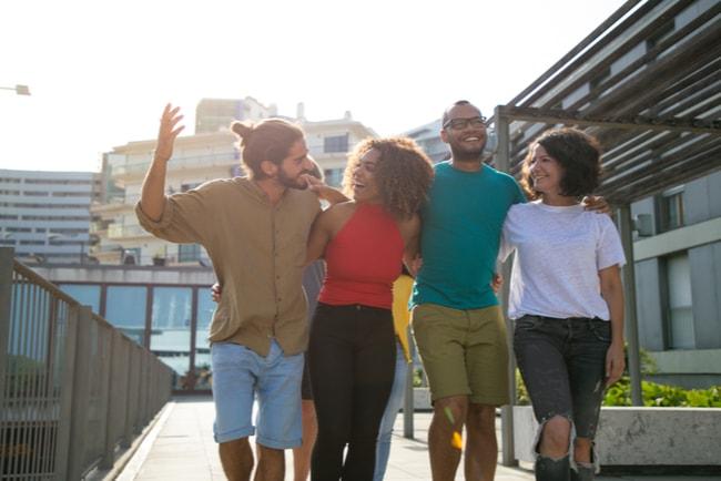 fyra glada vänner går tillsammans i fin stadsmiljö