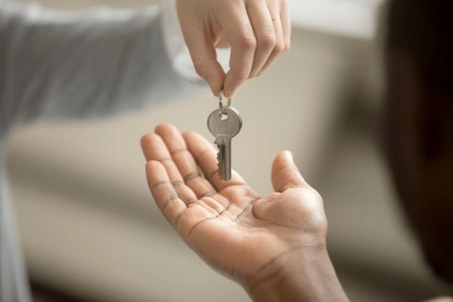 en hand räcker över nycklar till en annan hand
