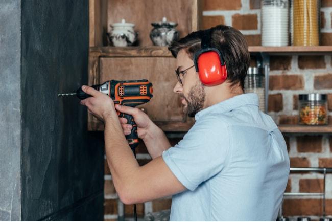 man med hörselkåpor borrar i lägenhetsvägg
