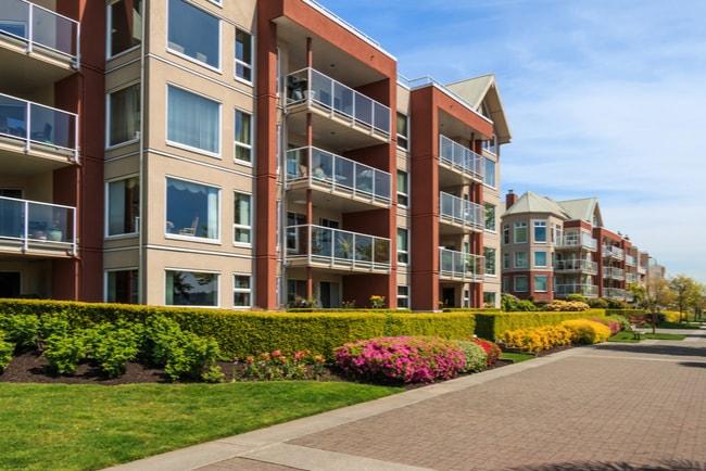 lägenhetshus med gräsmatta och blommor längs gata