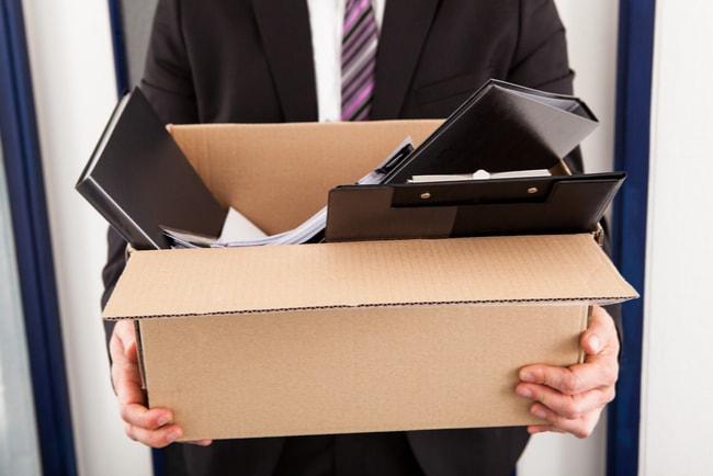 affärsman håller i kartong med kontorsprylar