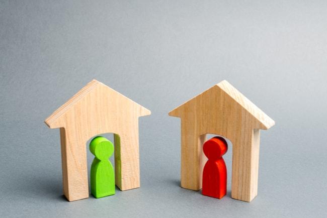 två miniatyrhus i trä med en grön och en röd figur