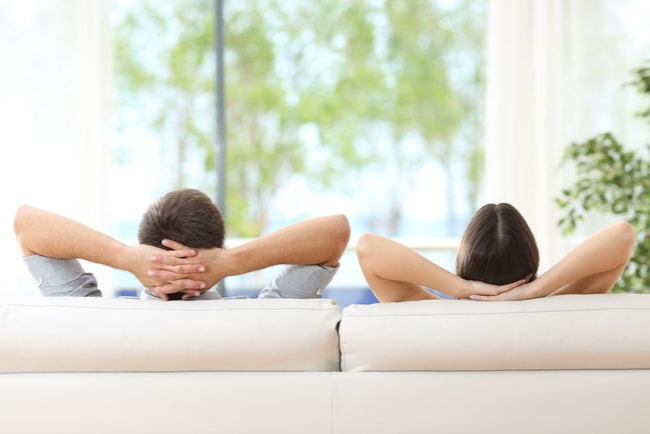 Par lutar sig tillbaka i soffa och tittar ut genom ett fönster.