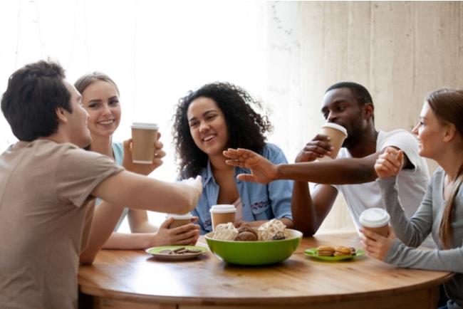 fem glada ungdomar umgås kring ett matbord