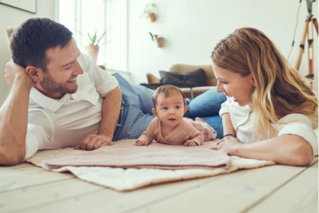 leende par och deras bebis ligger på sitt vardagsrumsgolv