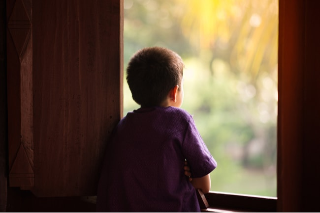 pojke tittar ut genom fönster