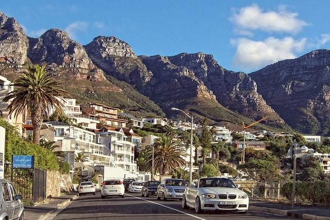 biltrafik genom kapstaden i sydafrika med bergspass i bakgrunden
