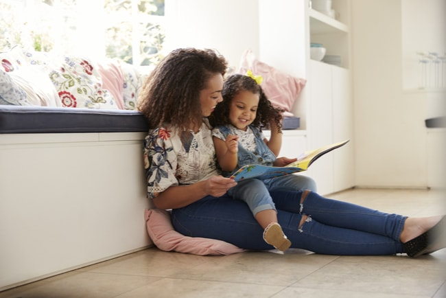 mamma läser en bok sittandes på golvet med sin dotter i knät