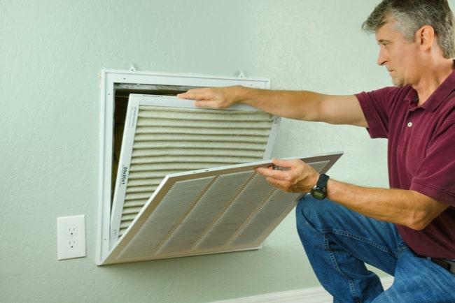 man som tar loss ventilationsfilter