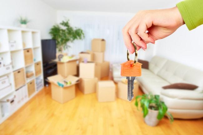 hand håller nyckel i lägenhet med flyttkartonger och möbler i bakgrunden.