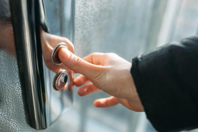 hand trycker på hissknapp