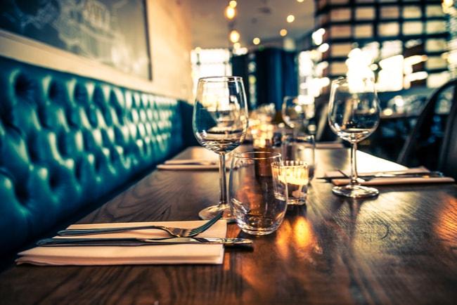 Mörkt bord på restaurang dukat med bestick och glas.