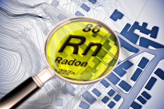 förstoringsglas med kemiska beteckningen för radon över planritning av stadsområde
