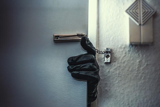 inbrottstjuv bryter sig in genom dörr med kedjelås