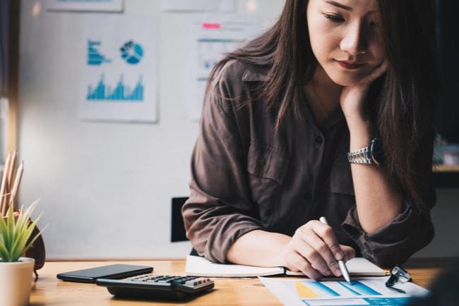 kvinna sitter vid skrivbord och beräknar skatt